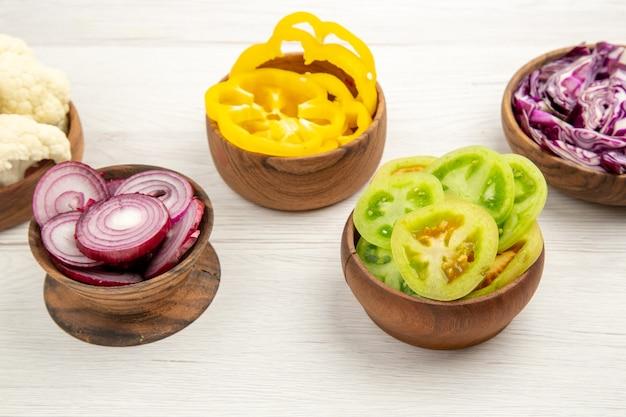 Vista inferior legumes picados pimentão tomate verde repolho vermelho cebola vermelha em tigelas de madeira na mesa branca