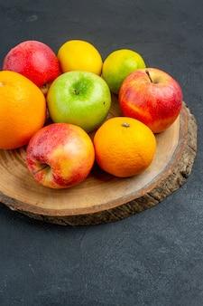 Vista inferior maçãs limão laranjas em placa de madeira em superfície escura