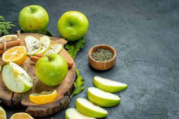 Vista inferior, maçãs verdes, paus de canela e rodelas de limão fatias de maçã na tábua de madeira em pó de hortelã seca em uma tigela pequena no espaço livre da mesa preta