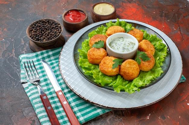 Vista inferior nuggets de frango alface e molho no prato, molhos e pimenta preta em tigelas pequenas faca e garfo na mesa escura