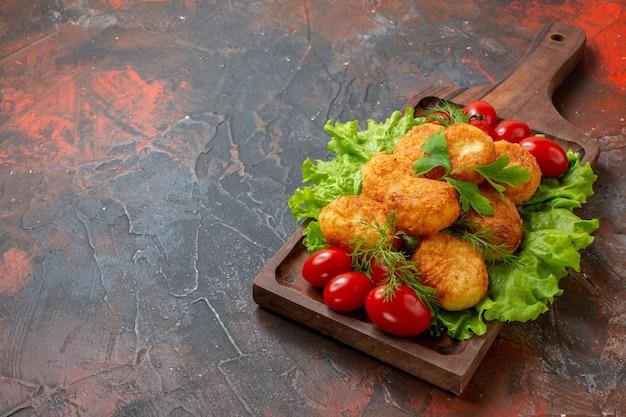 Vista inferior, nuggets de frango, tomate cereja, alface, numa tábua de madeira, na mesa escura