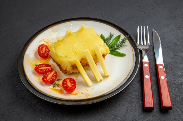 Vista inferior pão de queijo, tomate cereja e batata frita no prato, garfo e faca em fundo preto