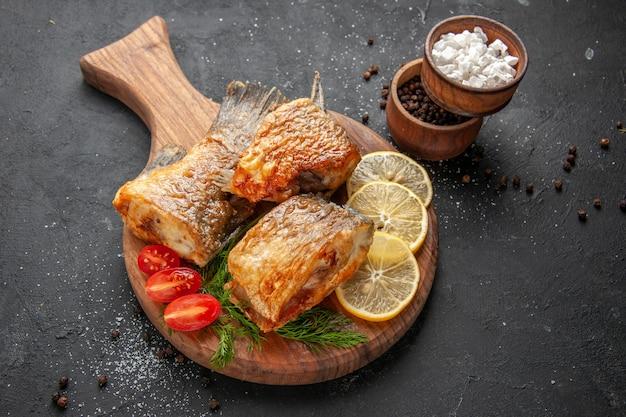 Vista inferior, peixe frito, fatias de limão cortam tomates cereja na tábua de cortar temperos diferentes em tigelas com fundo preto