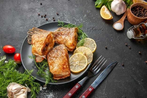 Vista inferior peixe frito pimenta preta em uma tigela rodelas de menta, garfo e faca na mesa preta