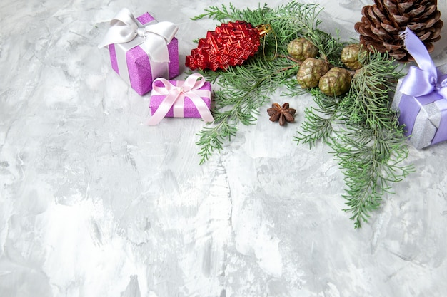 Vista inferior presentes de natal brinquedos de árvore de natal pinheiro galhos de árvore em fundo cinza espaço livre