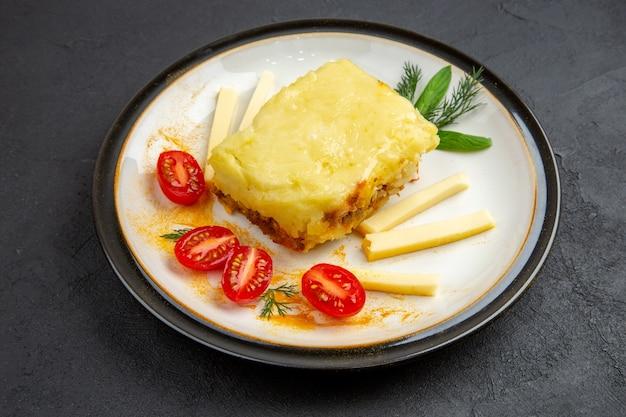 Vista inferior, saborosa lasanha, tomate cereja em prato redondo em fundo escuro