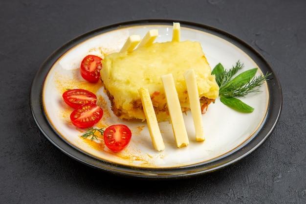 Vista inferior, saborosa lasanha, tomate cereja no prato em fundo escuro