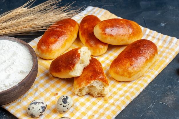 Vista inferior saborosos rolos de jantar em toalha de cozinha tigela de farinha ovos de codorna trigo na mesa copiar plac