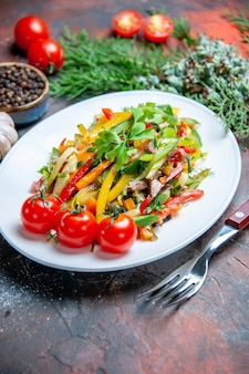 Vista inferior salada de vegetais em prato oval garfo tomate cereja pimenta preta em superfície vermelha escura