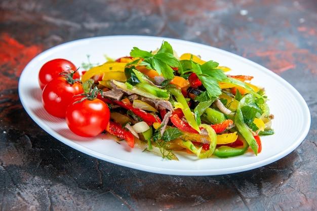Vista inferior, salada de vegetais, tomate cereja em prato oval em superfície vermelha escura isolada