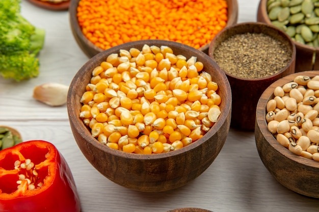 Vista inferior tigelas de madeira com sementes de milho feijão sementes de abóbora lentilhas pimenta preta tigela pimenta vermelha na mesa