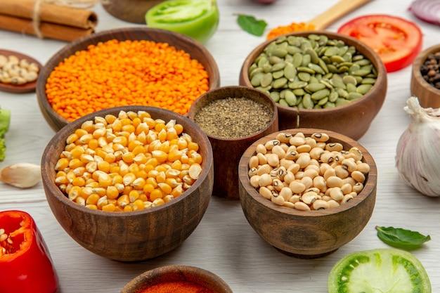 Vista inferior tigelas de madeira com sementes de milho feijão sementes de abóbora lentilhas tigela pimenta preta alho cinnamons