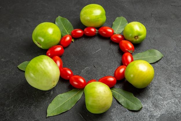 Vista inferior, tomate cereja, tomate verde e folhas de louro em fundo escuro