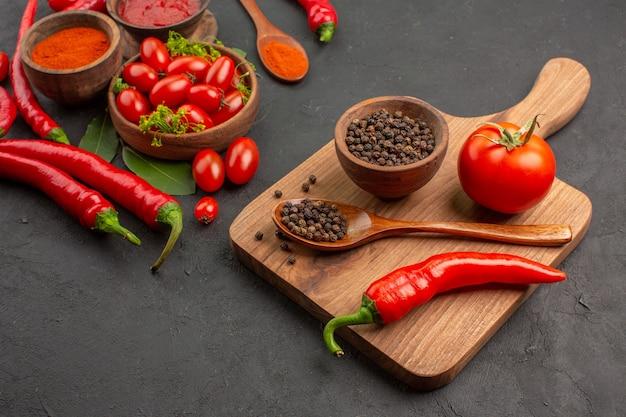 Vista inferior uma tigela de tomate cereja pimenta vermelha picante folhas de louro e uma tigela de pimenta preta uma colher de pau uma pimenta vermelha na tábua de cortar no fundo preto