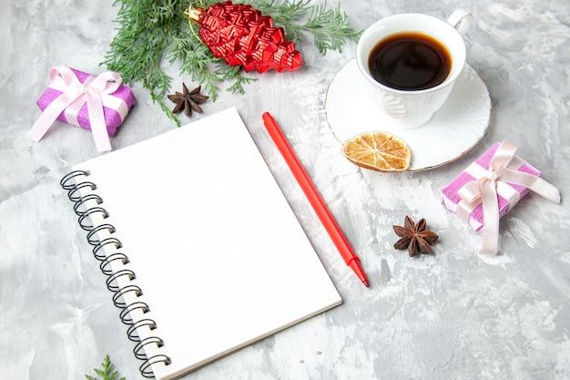 Vista inferior, uma xícara de chá, caderno, lápis, pequeno, presente, brinquedo, árvore de natal, em, fundo cinza