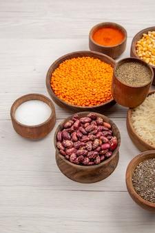 Vista inferior, várias especiarias, açafrão-da-índia, pimenta preta em pequenas tigelas, arroz, feijão, lentilha, mesa cinza