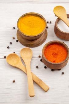 Vista inferior, várias especiarias, açafrão, pimenta vermelha, sal em pó em uma tigela pequena colheres de madeira com pimenta preta espalhada na mesa cinza