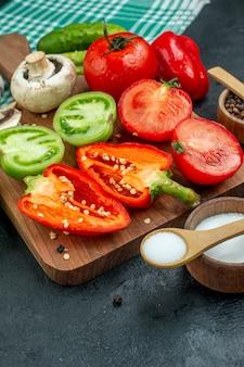 Vista inferior vegetais cogumelos tomates pimentões na tábua de cortar alho sal em tigelas colheres de madeira pepinos na mesa preta