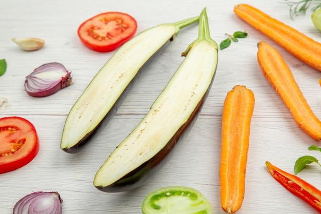 Vista inferior vegetais picados berinjela tomate cenoura cebola na mesa de madeira cinza