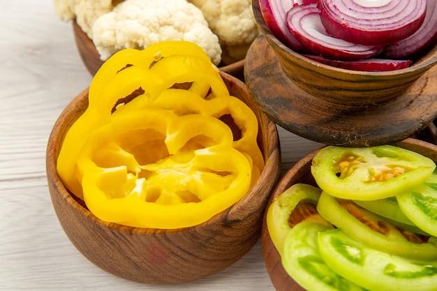 Vista inferior vegetais picados cortados pimentões amarelos cortados cebola cortados tomates verdes couve-flor em tigelas na mesa branca