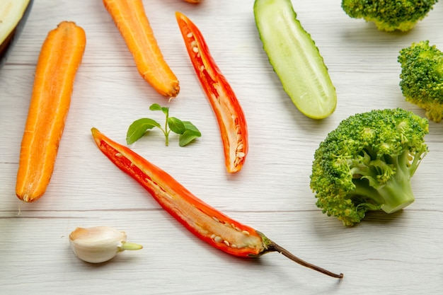 Vista inferior vegetais picados pepino brócolis cenoura pimenta na mesa cinza