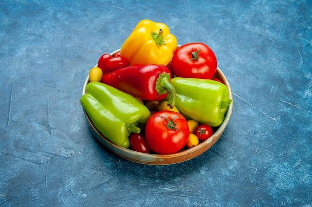 Vista inferior vegetais tomates cereja cores diferentes pimentões tomates cumcuat em uma bandeja de madeira na mesa azul