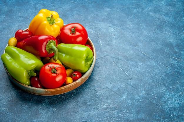Vista inferior vegetais tomates cereja cores diferentes tomates pimentões em uma bandeja de madeira na mesa azul com local de cópia