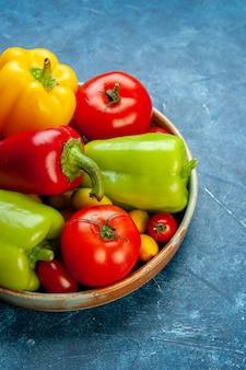 Vista inferior vegetais tomates cereja cores diferentes tomates pimentões em uma bandeja de madeira na mesa azul