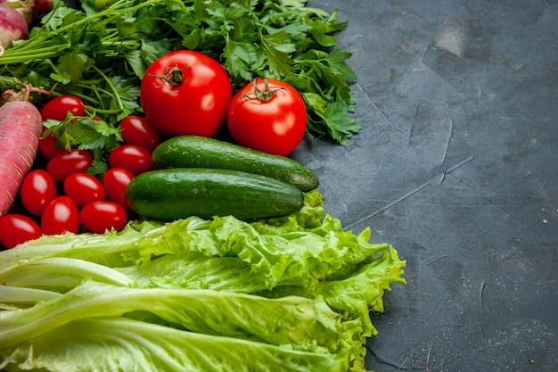 Vista inferior vegetais tomates cereja pepinos alface rabanete salsa tomates na superfície escura espaço livre