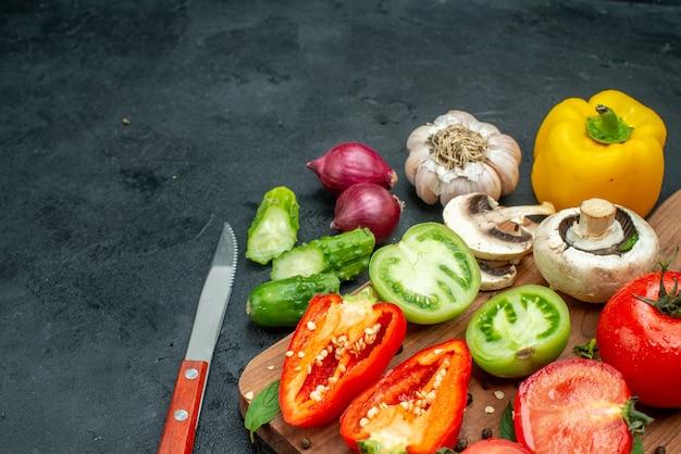 Vista inferior vegetais verdes e vermelhos tomates pimentão amarelo na tábua de cortar verdes em uma tigela faca pepinos cebola vermelha na mesa preta cópia local