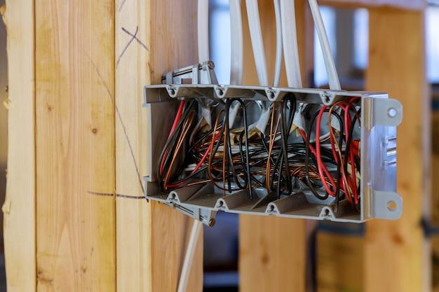 Vista interior de uma caixa elétrica com fiação em uma nova casa em vigas de madeira de construção