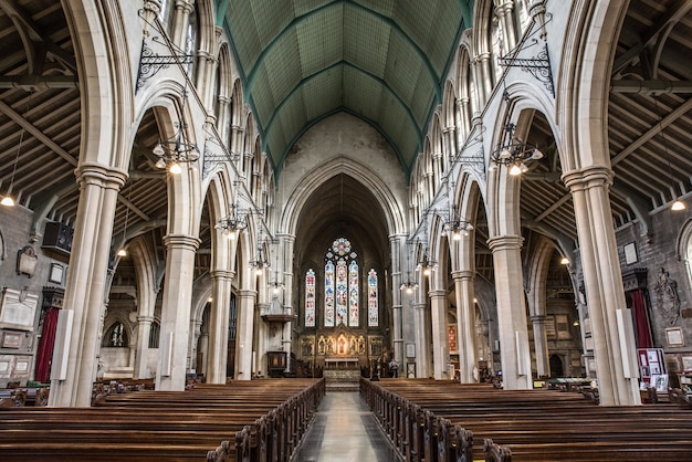 Vista interna de uma igreja com ícones religiosos nas janelas e arcos de pedra