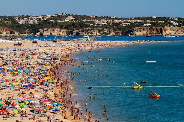Vista larga de uma praia aglomerada em portimao, portugal.