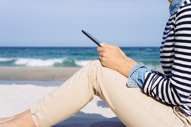 Vista lateral: a mulher de camisa listrada na praia, lendo um livro