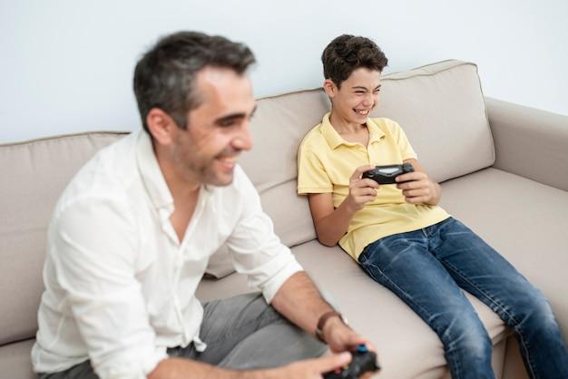Vista lateral adulto e criança brincando no sofá