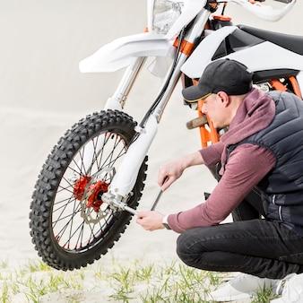 Vista lateral adulto masculino tentando reparar moto