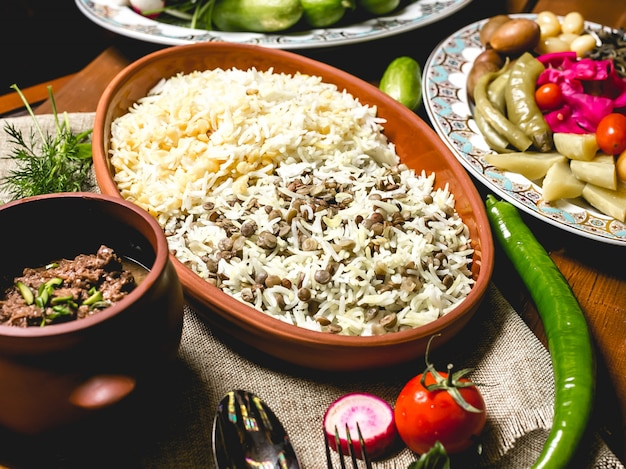 Vista lateral arroz cozido em um prato com carne em uma panela e legumes salgados