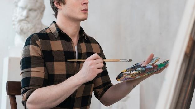 Vista lateral artista homem pintura sobre tela