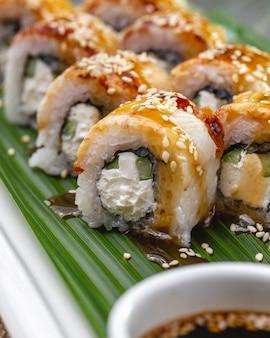 Vista lateral assada rolo de sushi de salmão com creme de queijo nori pepino e gergelim