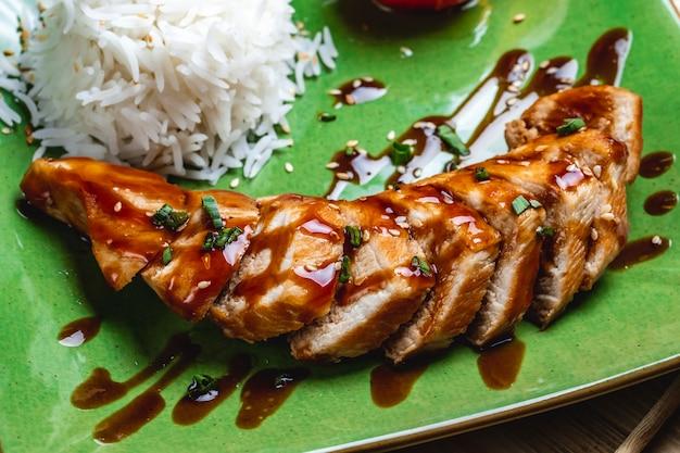 Vista lateral assado peito de frango com molho de cebola primavera sementes de gergelim e arroz em um prato