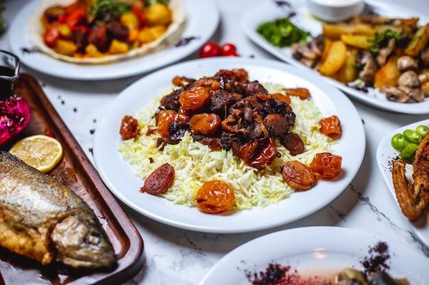 Vista lateral azedo pilaf com ensopado de carneiro chesntnuts e frutas secas em um prato