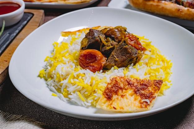 Vista lateral azedo pilau azedo frito carne com cebola castanhas frutas secas e bolo em um prato