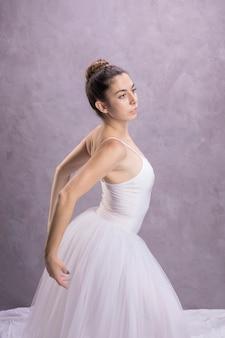 Vista lateral bailarina esticando as costas