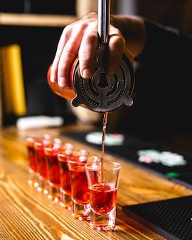 Vista lateral, barman, derrama, tiros, um, bebida, de, um, shaker