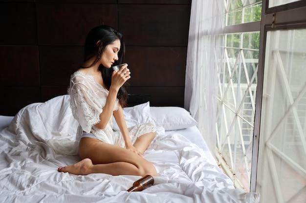 Vista lateral bêbada mulher asiática em lingerie branca, bebendo e segurando a garrafa de álcool enquanto está sentado na cama no quarto