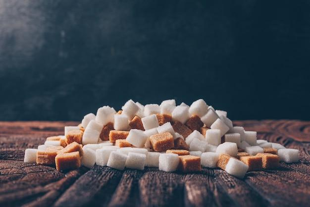 Vista lateral branco e cubos de açúcar mascavo na mesa escura e de madeira. horizontal