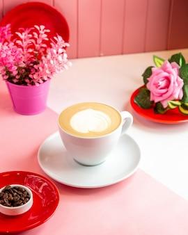 Vista lateral café cappuccino com uma decoração de espuma em forma de coração