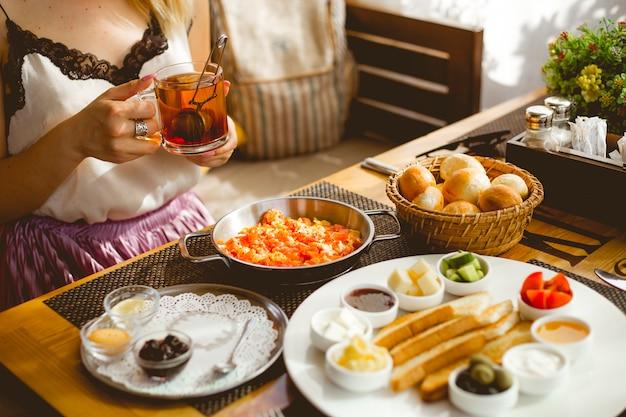 Vista lateral café da manhã conjunto ovos estilo azerbaijão com tomate geléia de torrada mel fresco tomate pepino queijo pão francês pães e chá preto em um copo