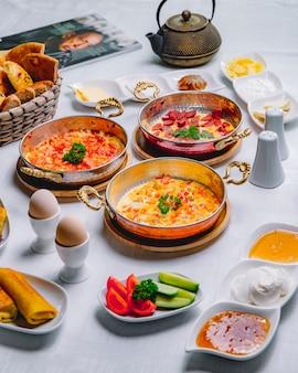 Vista lateral café da manhã servido ovos mexidos com tomate com omelete de legumes omelete com linguiça em uma panela