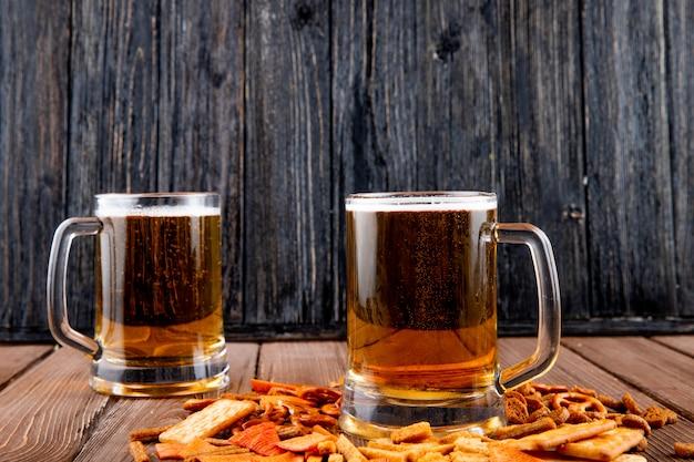 Vista lateral canecas de cerveja com batatas fritas e biscoitos na mesa de madeira